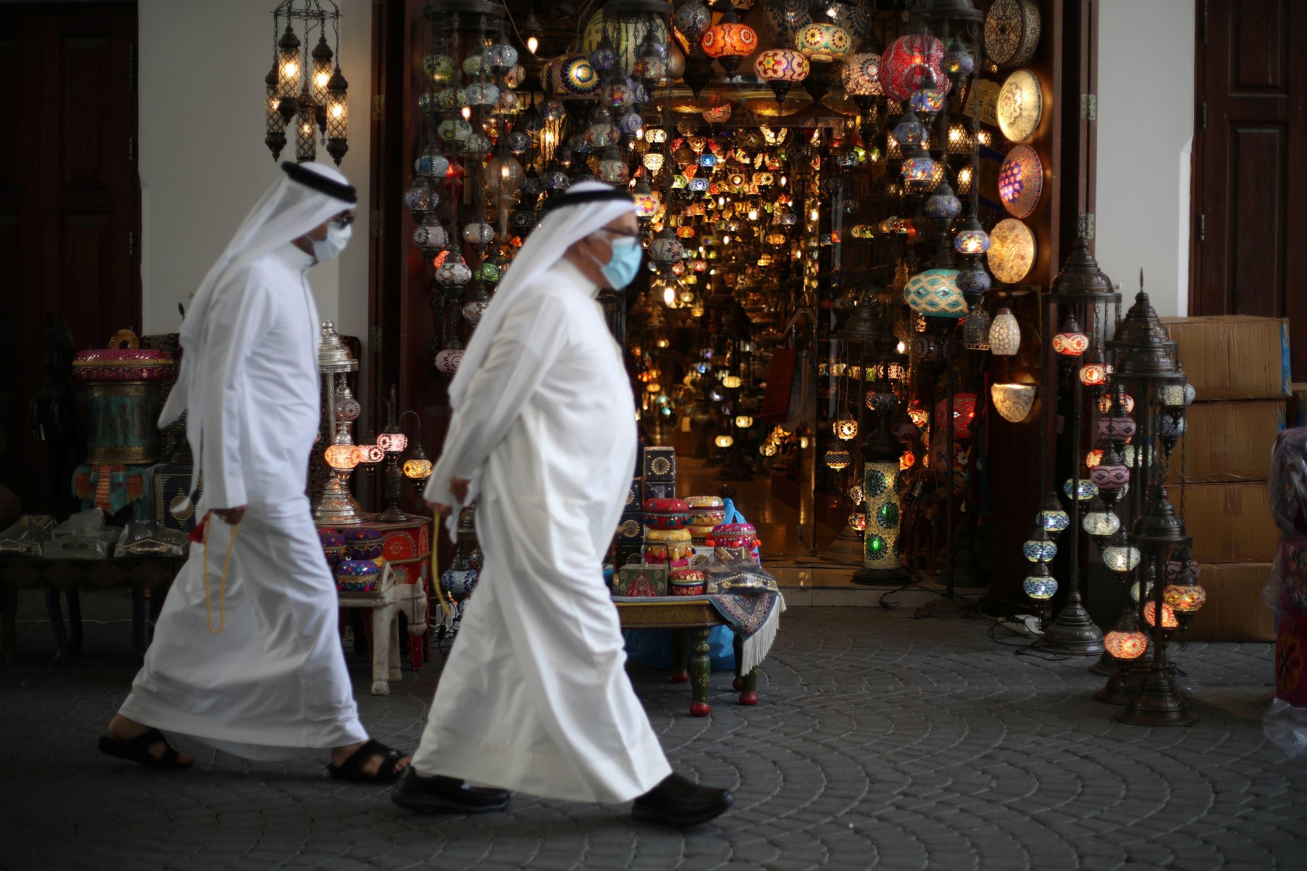 رجال يرتدون كمامات في أحد أسواق المنامة