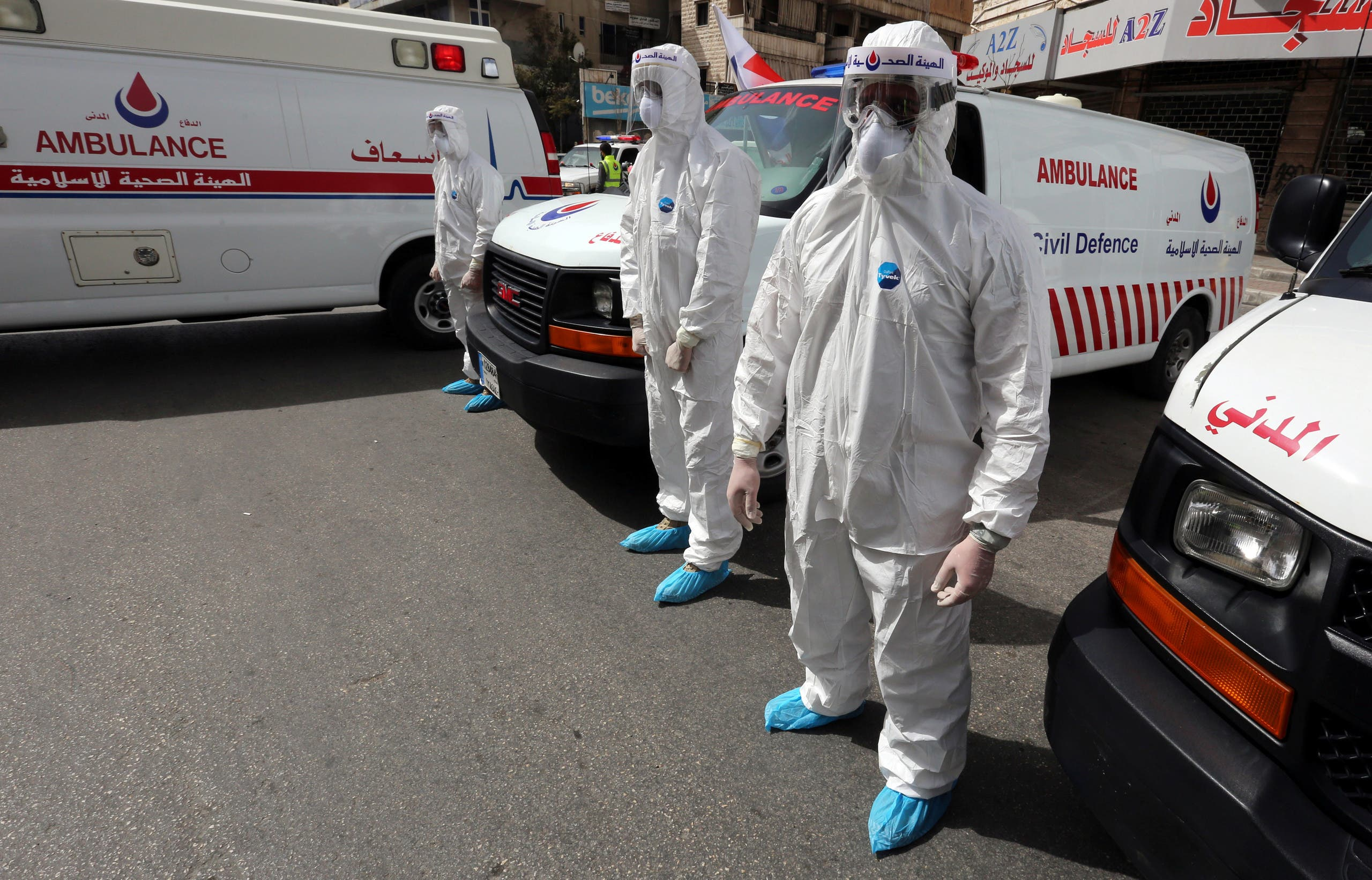 Islamic health unit personnel wearing protective gear stand near ambulances as part of preparations to help tackling the coronavirus disease (COVID-19) outbreak, during a media tour organised by Hezbollah officials in Beirut's southern suburb. (Reuters)
