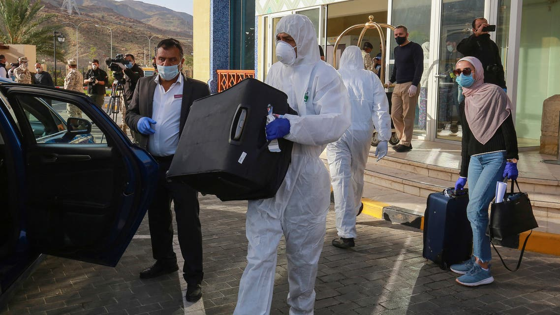 A worker helps a mask-clad woman with her baggage as she prepares to leave a Dead Sea resort where she has been quarantined for 14 days, approximately 60 kilometres sout of the Jordanian capital Amman on March 30, 2020. Jordanian authorities started to take home about 5,000 people quarantined in hotels to guard against the spread of coronavirus since their return to the country two weeks ago.
