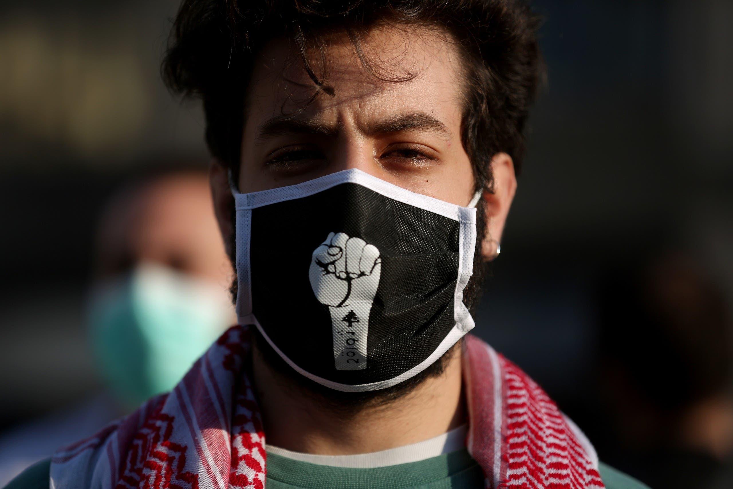 """متظاهر في لبنان يضع كمامة عليها علامة """"الثورة"""""""