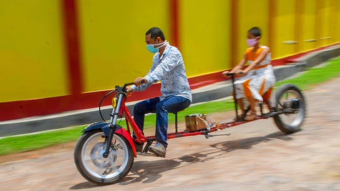Self-made automobile engineer Partha Saha (L) tries his modified bike designed for social distancing as a preventive measure against the spread of the COVID-19 coronavirus with his daughter Pragya Saha in front of their house. (AFP)