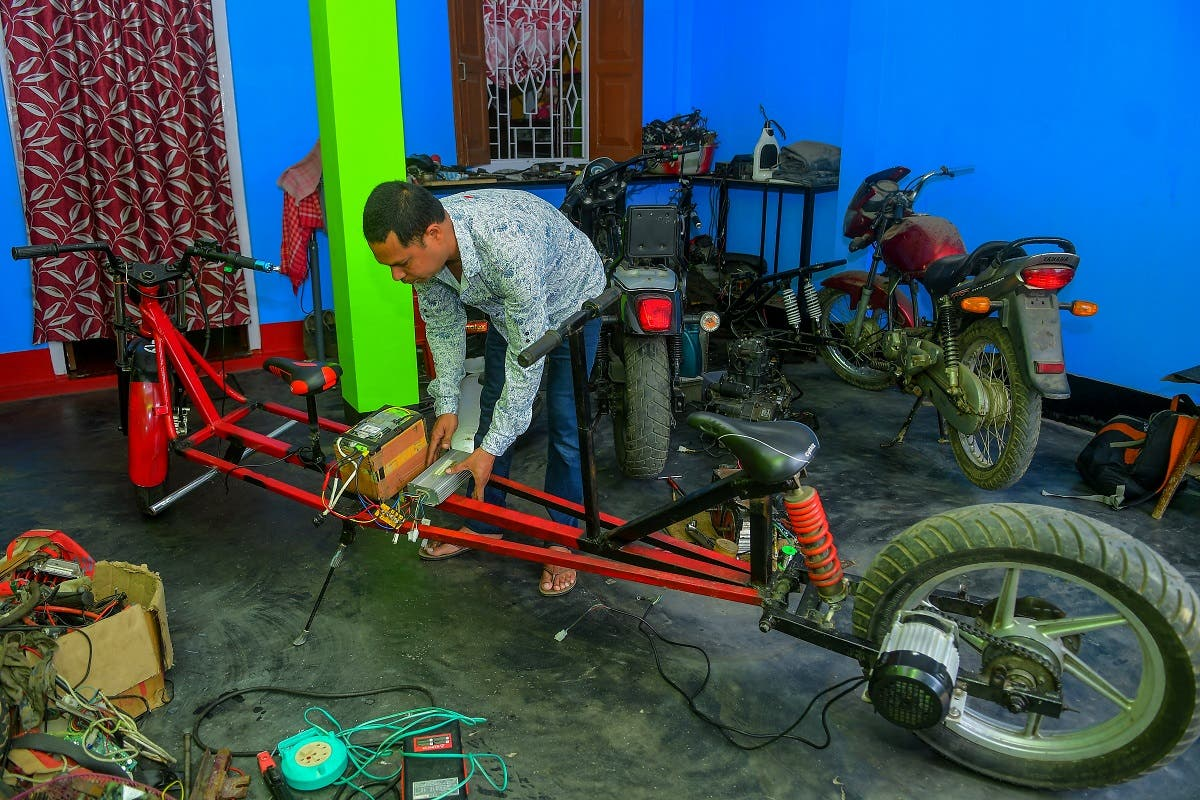 Self-made automobile engineer Partha Saha assembles his modified bike designed for social distancing as a preventive measure against the spread of the COVID-19 coronavirus inside his garage at his house, in Aralia village on the outskirts of Agartala. (AFP)