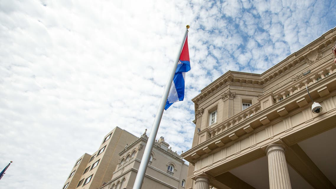 Cuban Foreign Minister Bruno Rodriguez, right, stands and faces the Cuban flag after raising it over their new embassy in Washington on July 20, 2015. (File photo: AP)