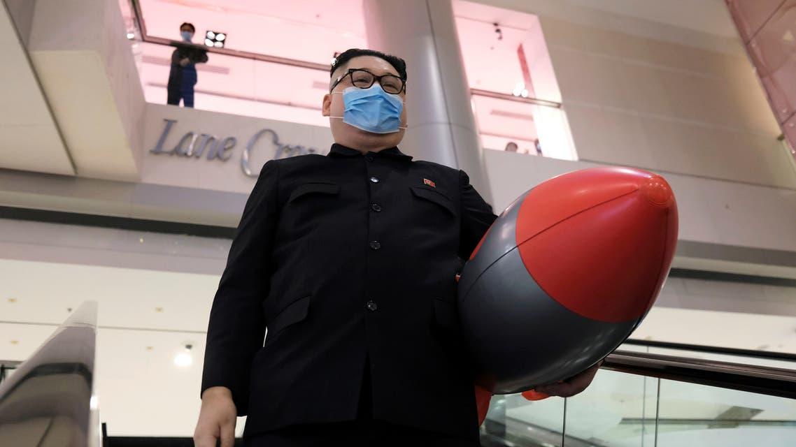 متظاهر صيني أسترالي شبيه بالزعيم الكوري الشمالي في هونغ كونغ يرتدي كمامة مقلداً كيم (أرشيفية- رويترز)