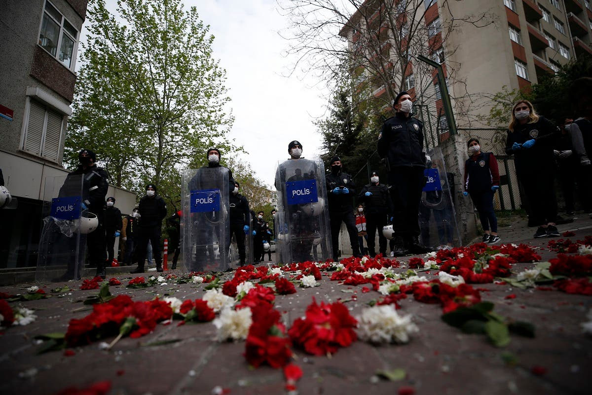 Turkish police officers, wearing face masks for protection against coronavirus, stand behind carnations left by demonstrators during May Day protests in Istanbul, on May 1, 2020. (AP)