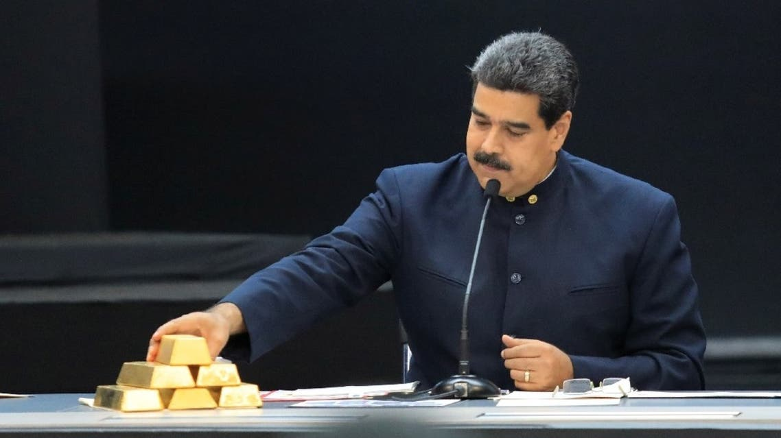 Venezuela's President Nicolas Maduro touches a gold bar as he speaks during a meeting with the ministers responsible for the economic sector at Miraflores Palace in Caracas, Venezuela, March 22, 2018. (Reuters)