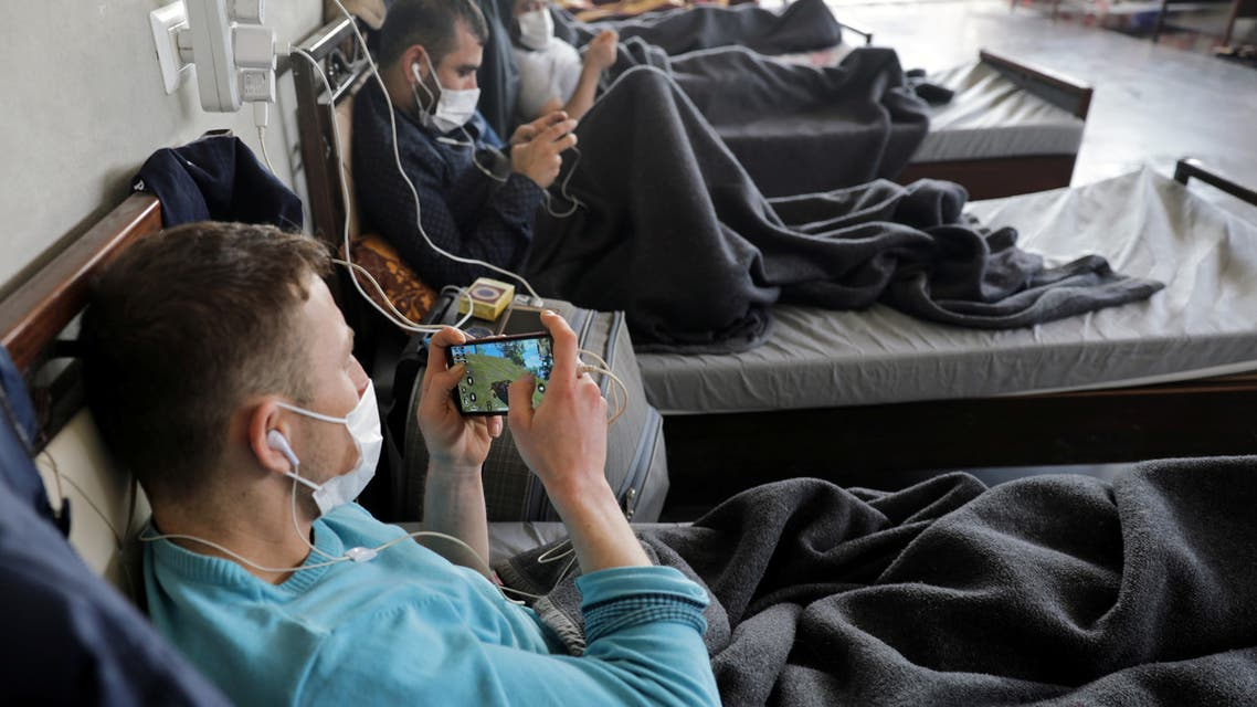 Men under quarantine wearing medical masks are seen playing video games in a quarantine site in Syria's northwest. (Reuters)