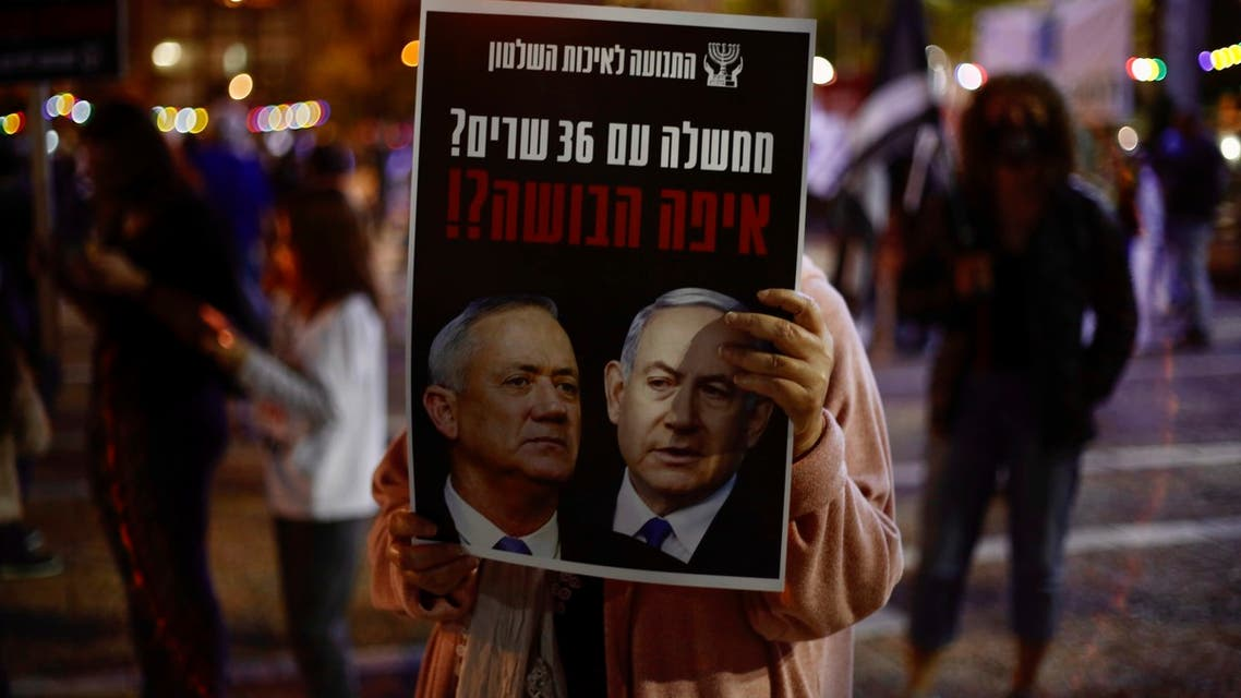 A woman holds a poster of Israeli Prime Minister Benjamin Netanyahu, right, and Benny Gantz, left, that read 'a government with 36 ministers? Where is the shame?' during a protest at Rabin square, in Tel Aviv, on Saturday, May 2, 2020. (AP)