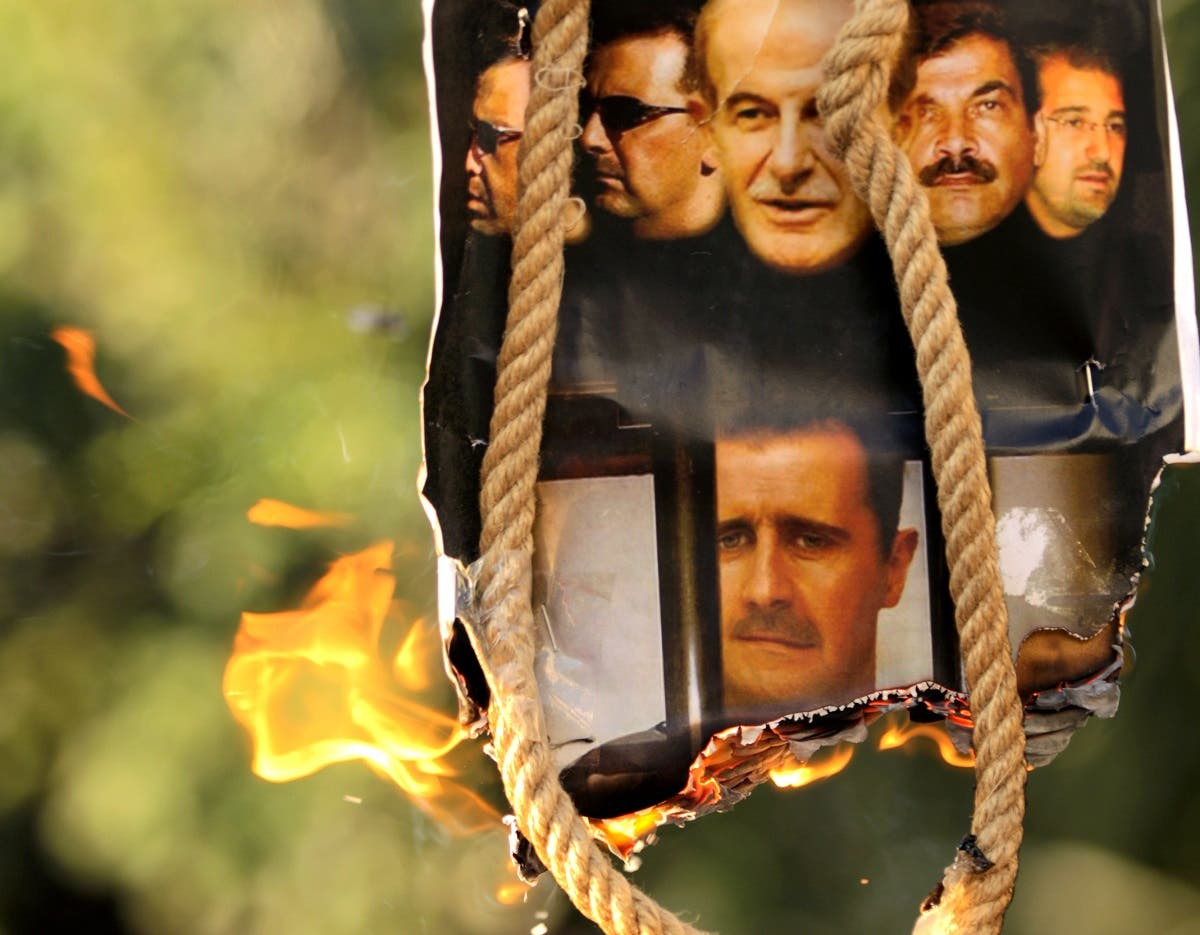 A makeshift gallows with a poster shows the pictures of former Syrian president Hafez al-Assad (top-C), his sons current President Bashar al-Assad (2nd L and bottom C) and Maher (L), their brother in-law General Assef Shawkat (2nd R) and businessman Rami Makhluf (R). (File photo: AFP)