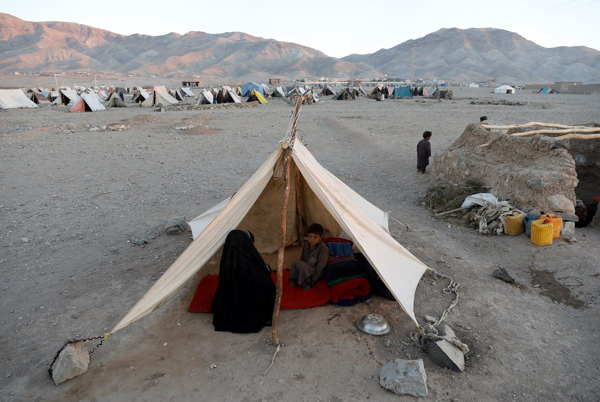 Internally displaced Afghan family sits inside a tent at a refugee camp in Herat province, Afghanistan. (Reuters)