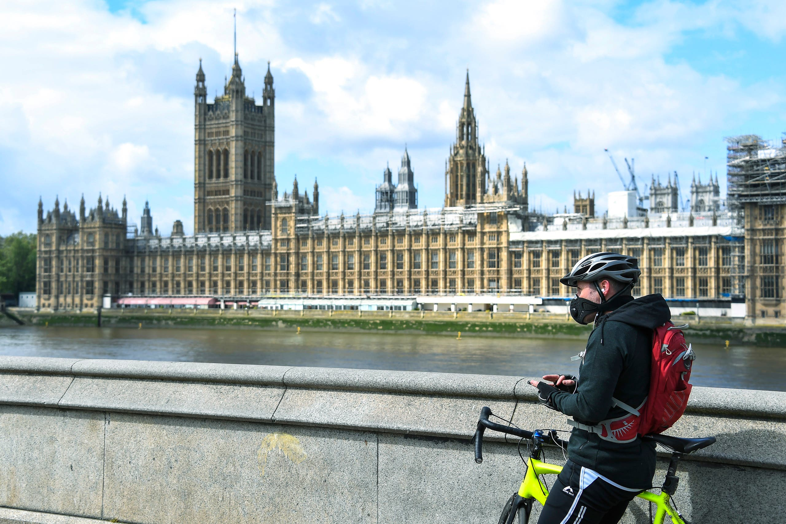 A man stands with his bike, on the south bank of the River Thames in London. (File photo: AP)