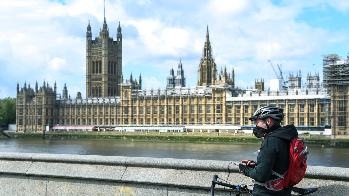 A man stands with his bike, wearing a protective mask to protect against coronavirus, on the south bank of the River Thames, against the backdrop of the Houses of Parliament, as the country continues its lockdown to curb the spread of coronavirus, in London on May 1, 2020. (AP)