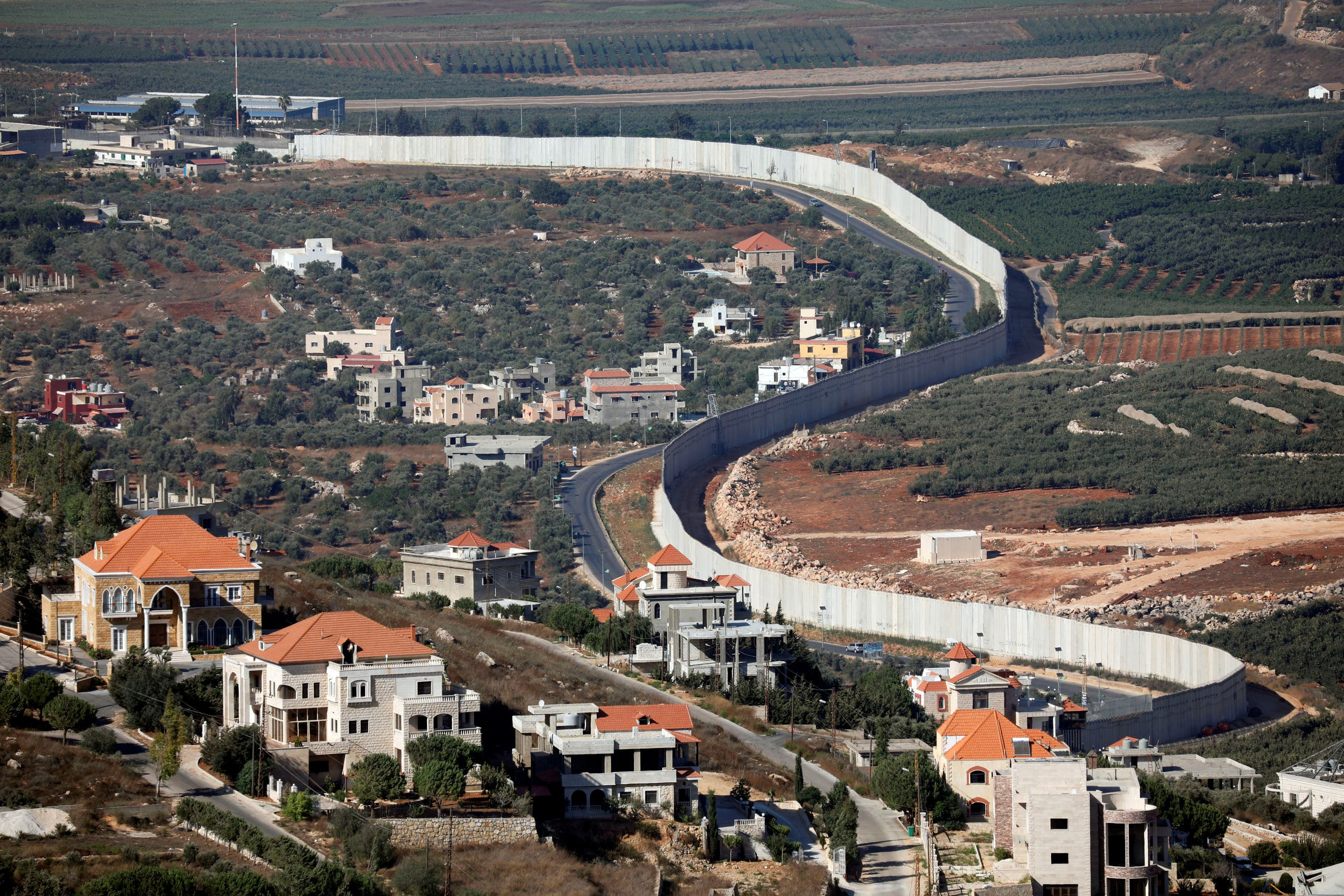 Houses and cars are seen in the Lebanese village of Adaisseh next to the Israel-Lebanon border, as seen from Kibbutz Misgav Am in northern Israel August 26, 2019. (Reuters)