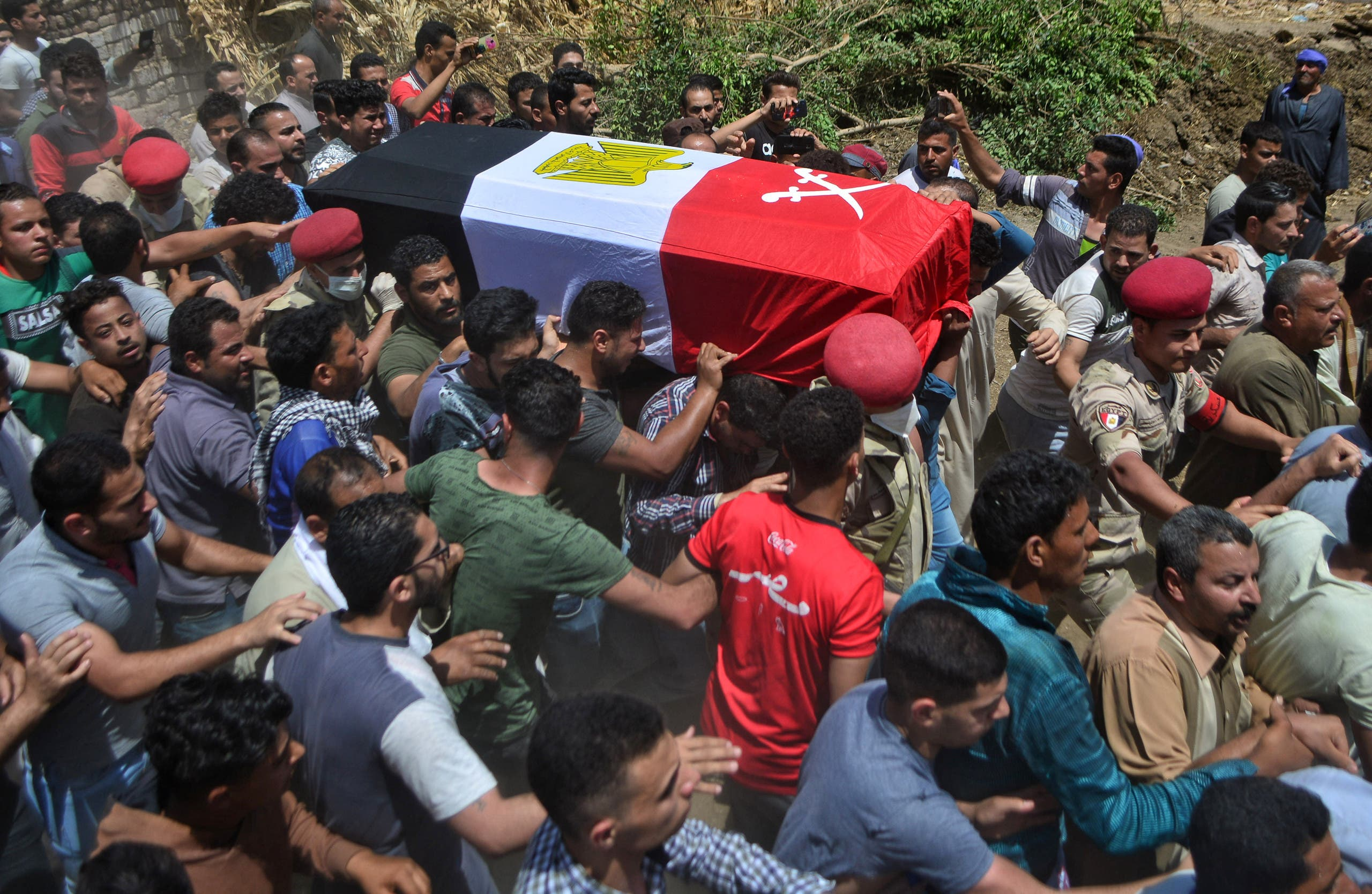 Mourners carry the coffin of Egyptian soldier Alaa Emad during his funeral in the village of Abwan in the Minya province on May 1, 2020, as his body was returned after he was killed in an explosion targeting an armored vehicle near Bir al-Abed in North Sinai. (AFP)