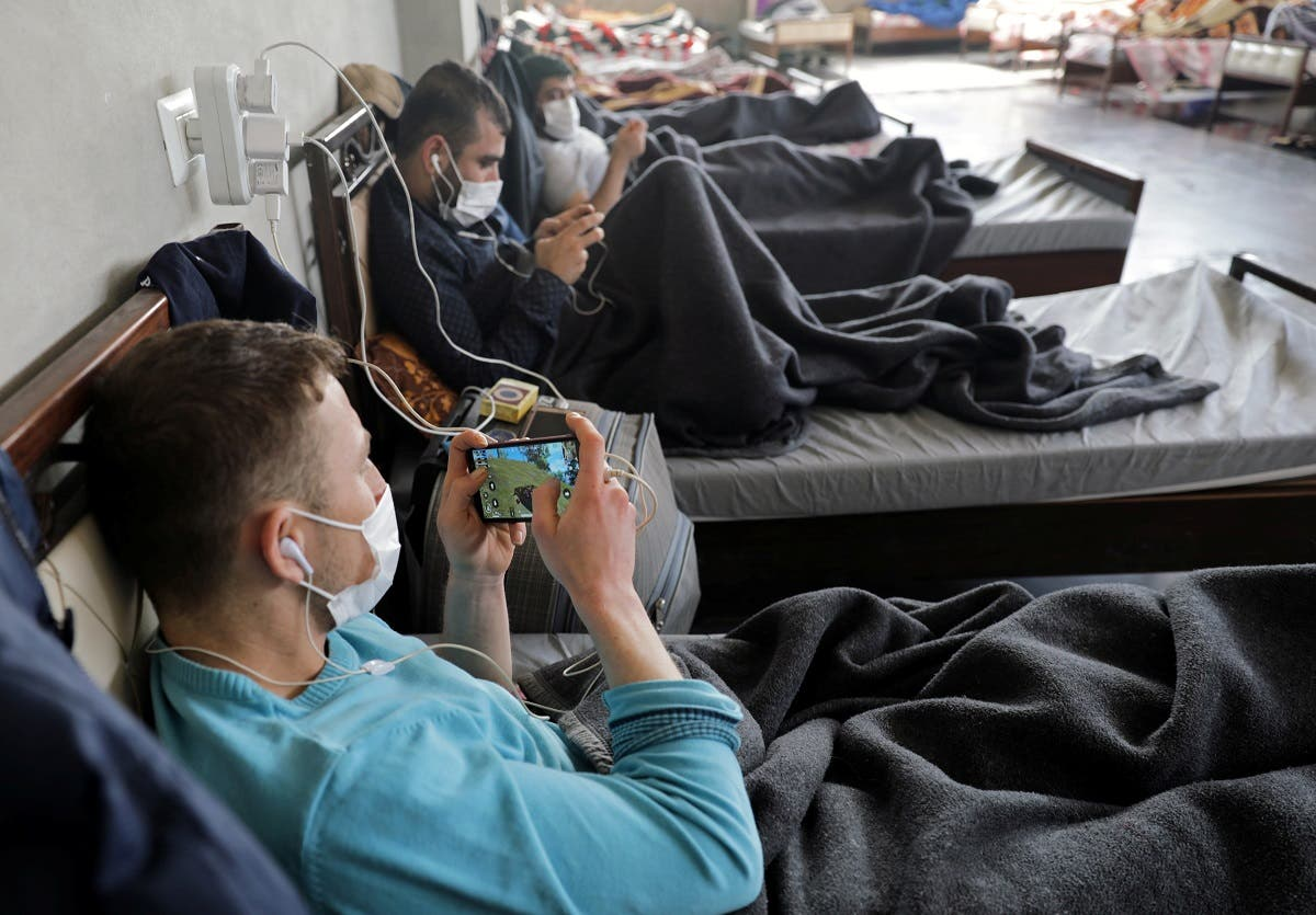 A Syrian man wearing a face mask plays a game on a mobile phone at a quarantine center in the town of Jisr al-Shughour in Idlib province, Syria April 30, 2020. (Reuters)