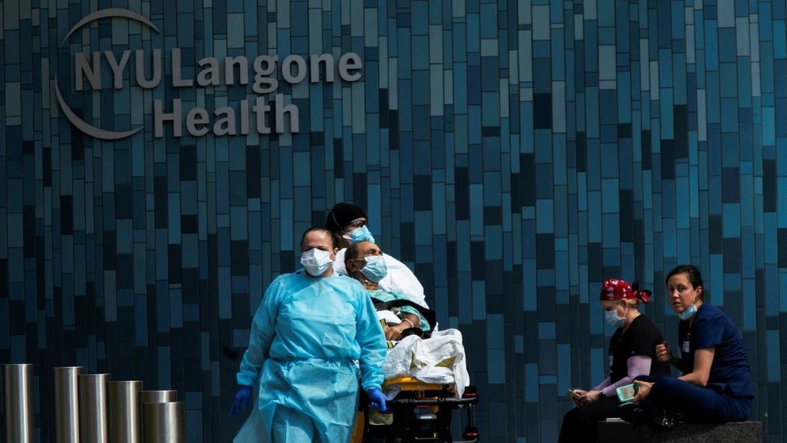 Health workers move a patient wearing a face mask at the at NYU Langone Hospital, during the outbreak of the coronavirus disease (COVID-19) in the Manhattan borough of New York City. (Reuters)