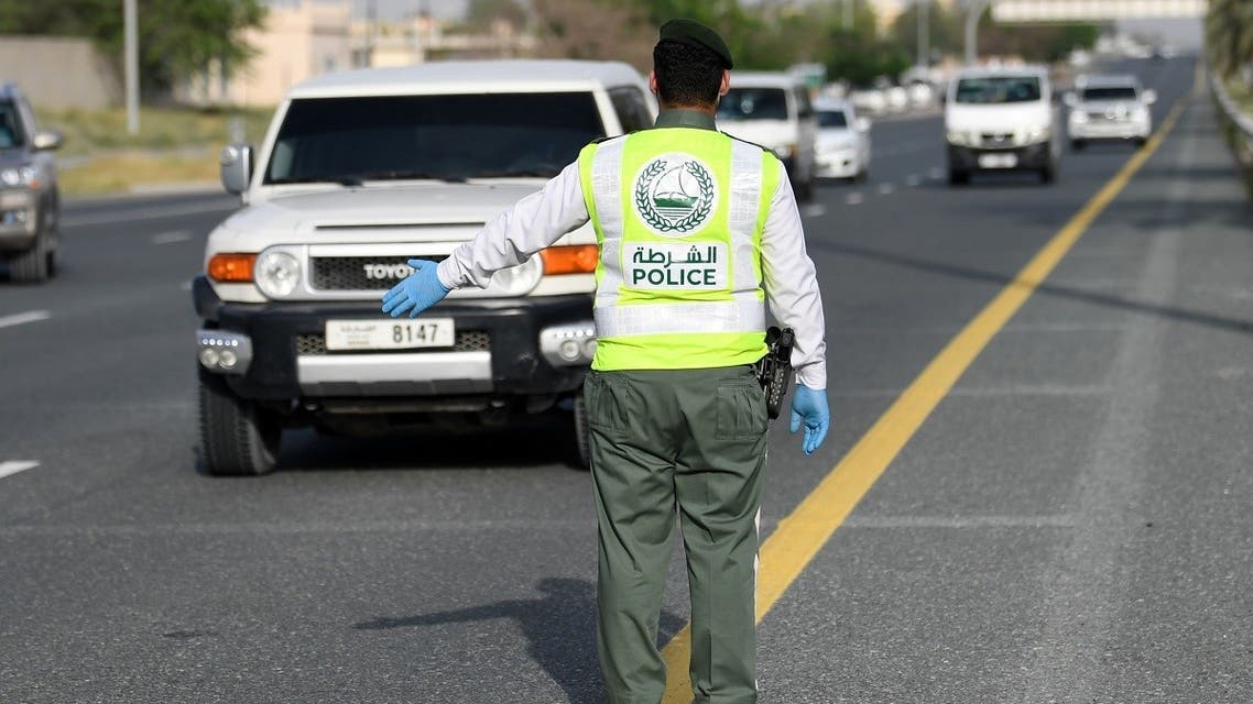 A policeman stops vehicles at a security checkpoint to examine passengers for exit permits, as people are only allowed essential travel due to a lockdown imposed by the UAE government as a measure during the COVID-19 coronavirus pandemic, in al-Khawaneej district of the gulf emirate of Dubai on April 9, 2020. (AFP)