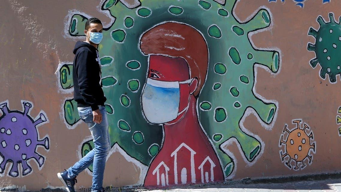 A Palestinians man wearing a face mask walks past a mural depicting the coronavirus COVID-19 coronavirus pandemic, in Gaza City. (File photo: AFP)