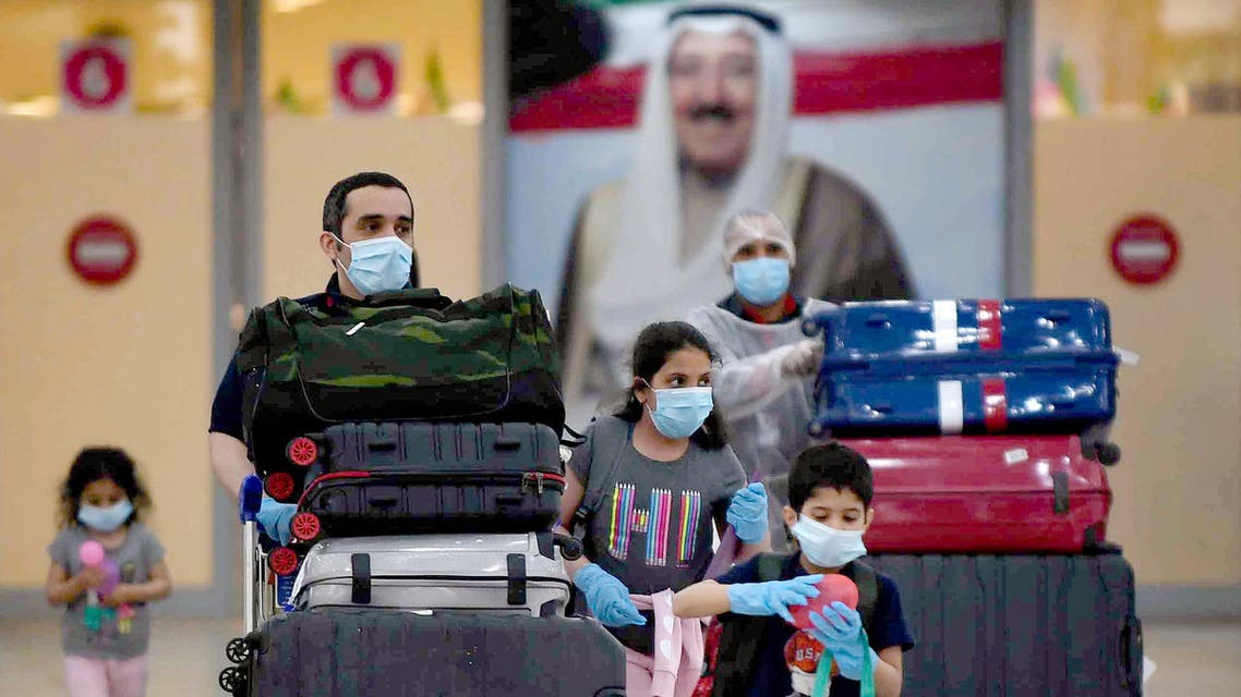 Kuwaiti nationals arrive at the Kuwait International Airport, south of the capital Kuwait City, after a rapatriation plan for citizens stranded abroad was put together by the authorities, on May 3, 2020, during the novel coronavirus pandemic crisis. Behind them hangs a poster of the Emir of Kuwait Sheikh Sabah Al-Ahmad Al-Jaber Al-Sabah. All incoming citizens will be required to undergo home quarantine for 14 consecutive days.