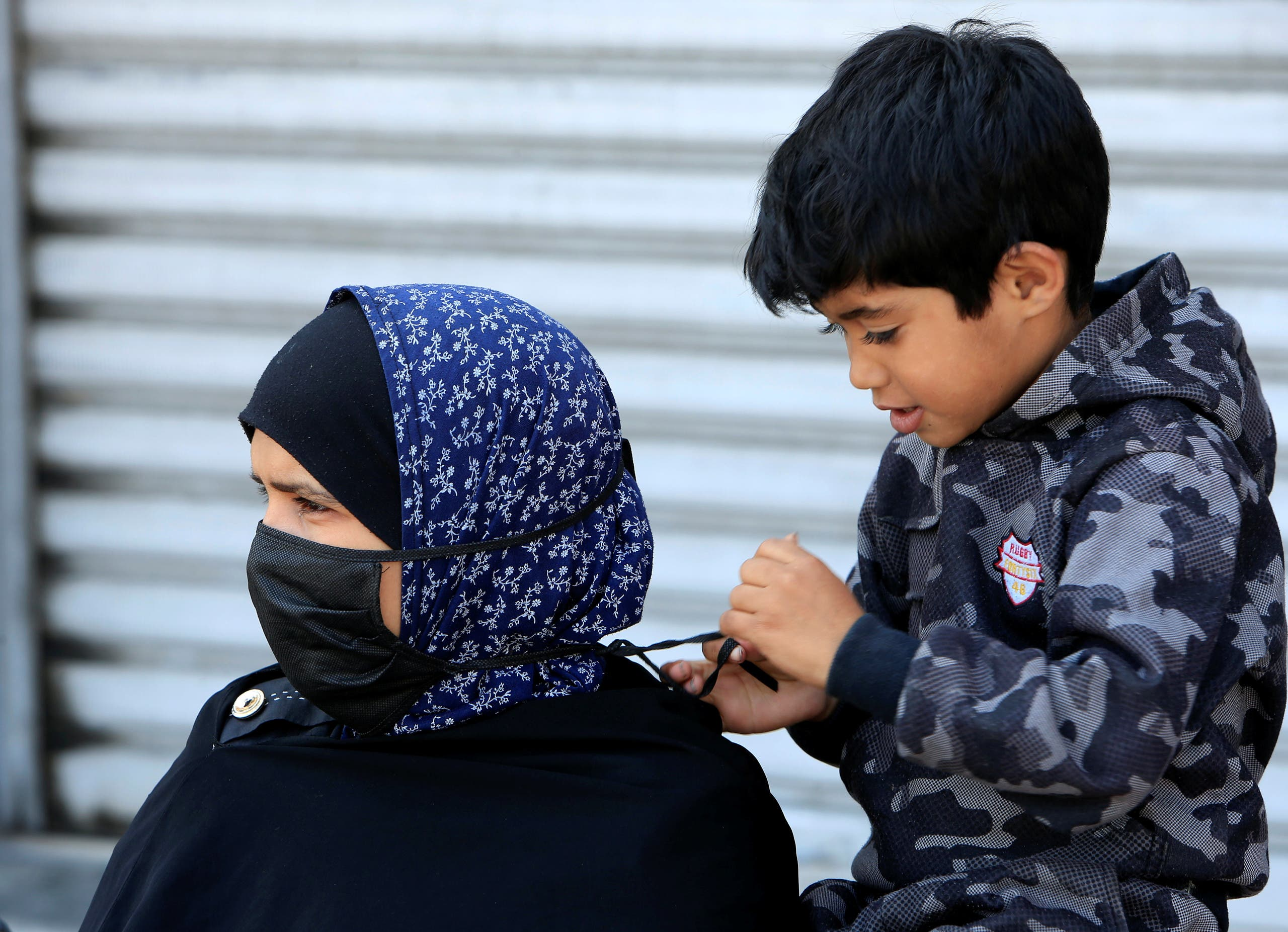 A boy helps his mother to put on a mask, during a countrywide lockdown to combat the spread of coronavirus disease (COVID-19) in Sidon, Lebanon April 28, 2020. (Reuters)