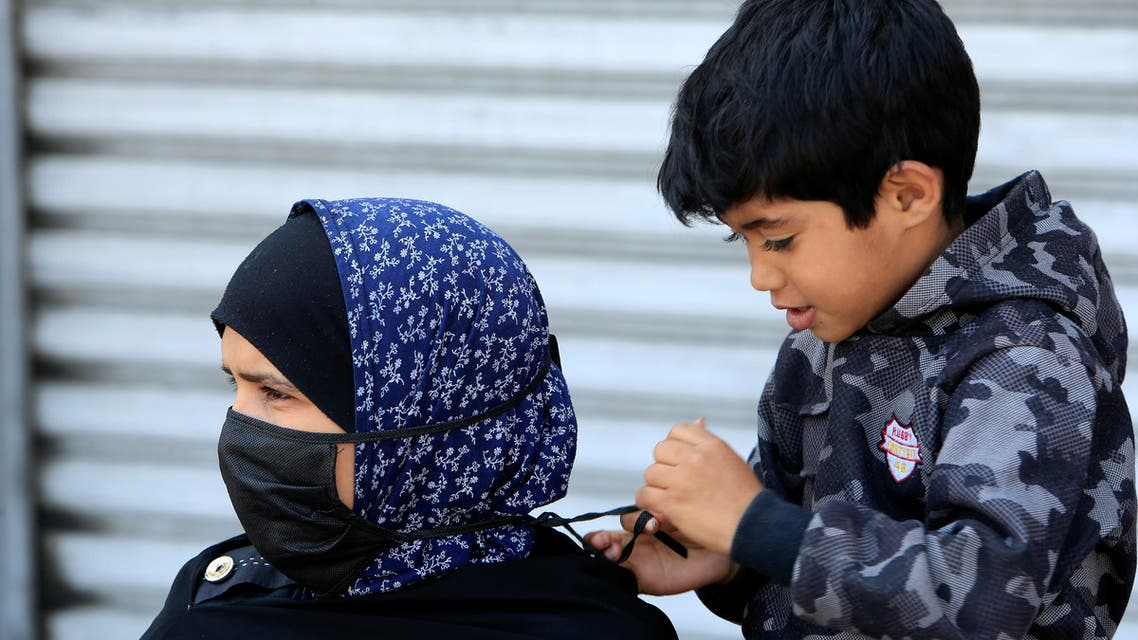A boy helps his mother to put on a mask, during a countrywide lockdown to combat the spread of coronavirus disease (COVID-19) in Sidon, Lebanon April 28, 2020. REUTERS/Ali Hashisho