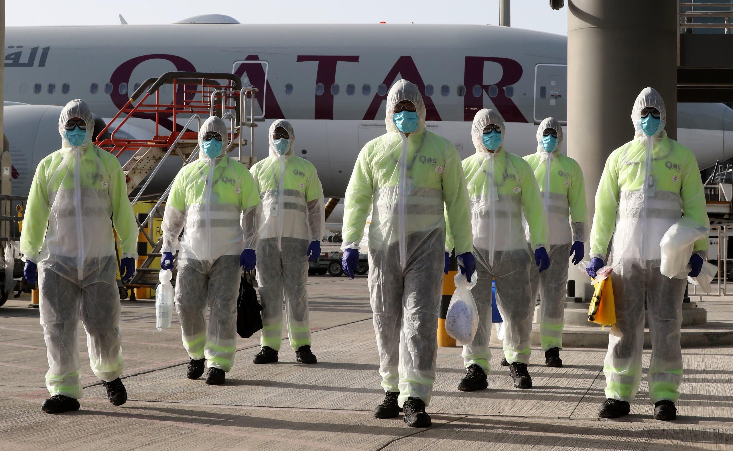 عمّال في مطار الدوحة يرتدون لباساً واقياً