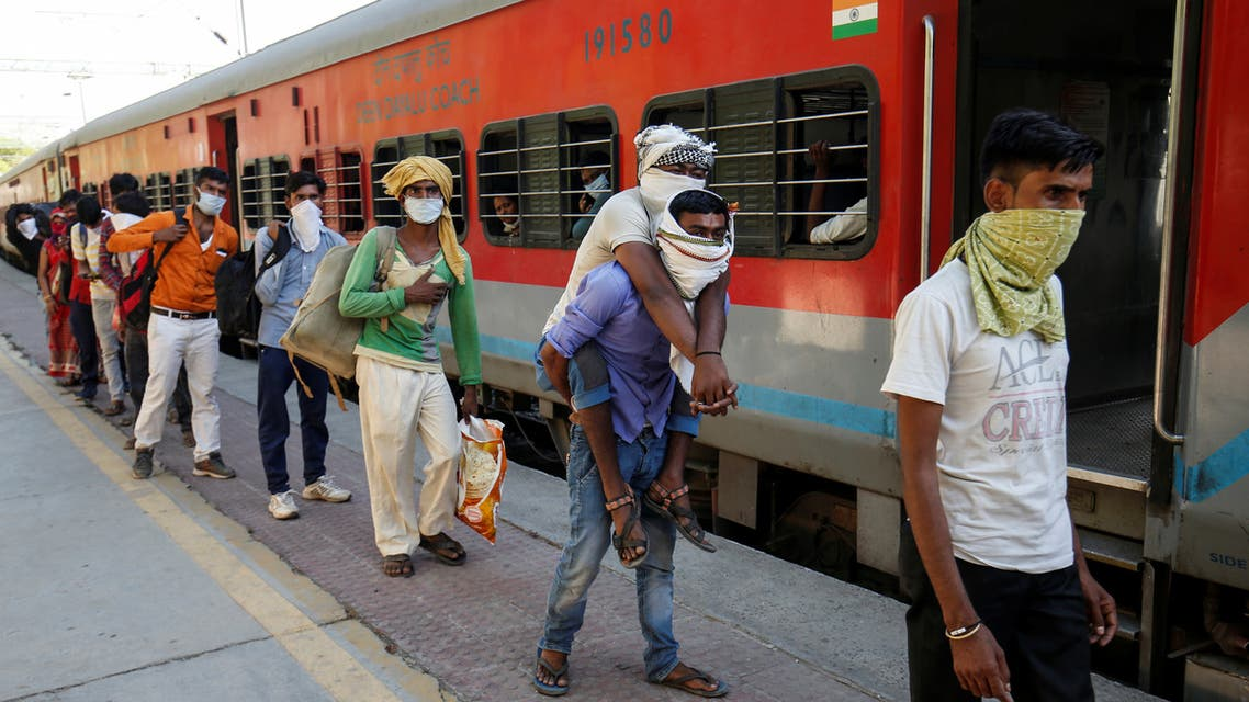 Migrant workers, who were stranded in the western state of Gujarat due to a lockdown imposed by the government to prevent the spread of coronavirus disease (COVID-19), wait to board a train at a railway station to leave for their home state of Uttar Pradesh, in Ahmedabad, India. (Reuters)