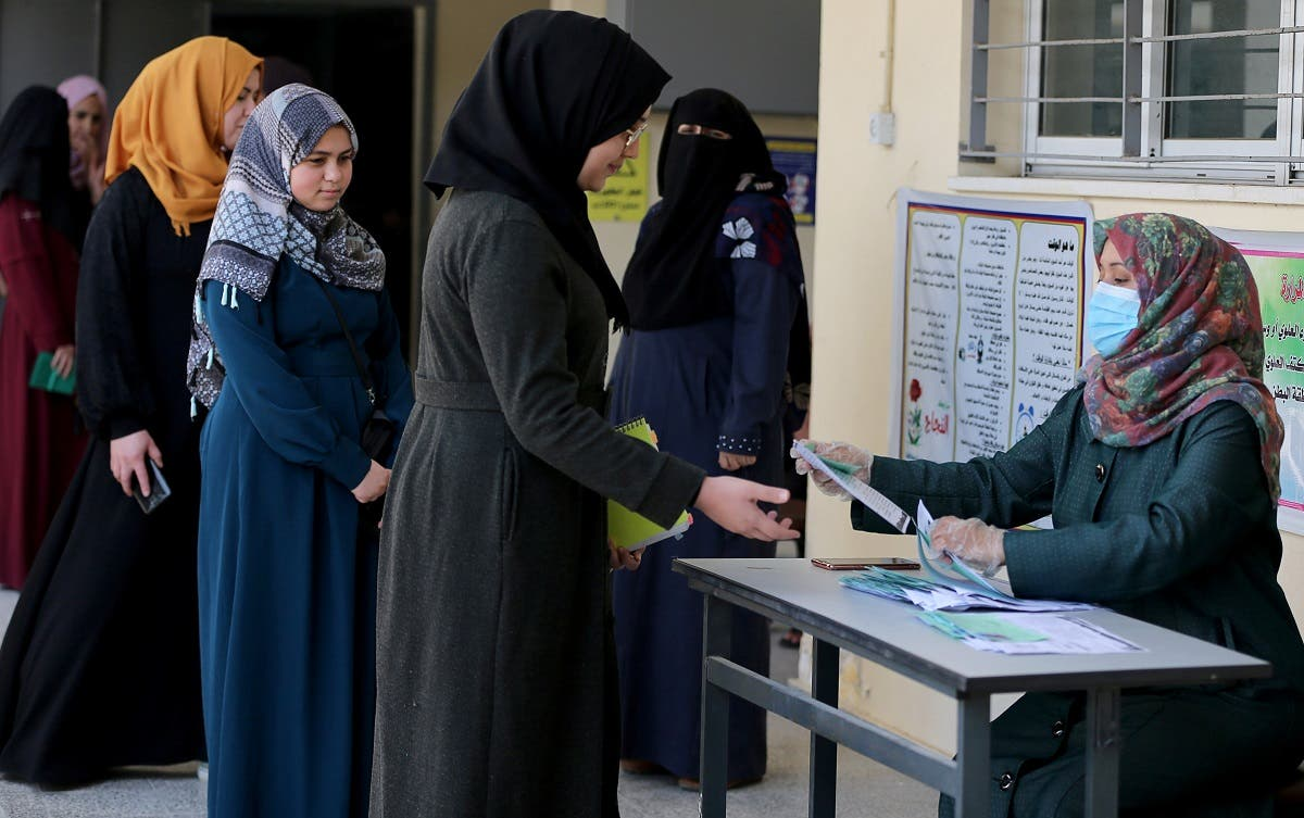 Palestinian high school students receive exam seating card information amid concerns about the spread of the coronavirus disease, in Gaza. (Reuters)