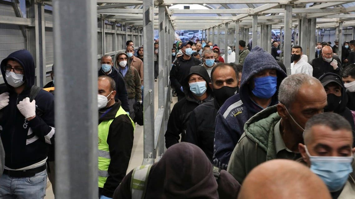 Palestinian labourers queue to enter Israel through the Mitar checkpoint in the occupied West Bank city of Hebron, on May 3, 2020. (AFP)