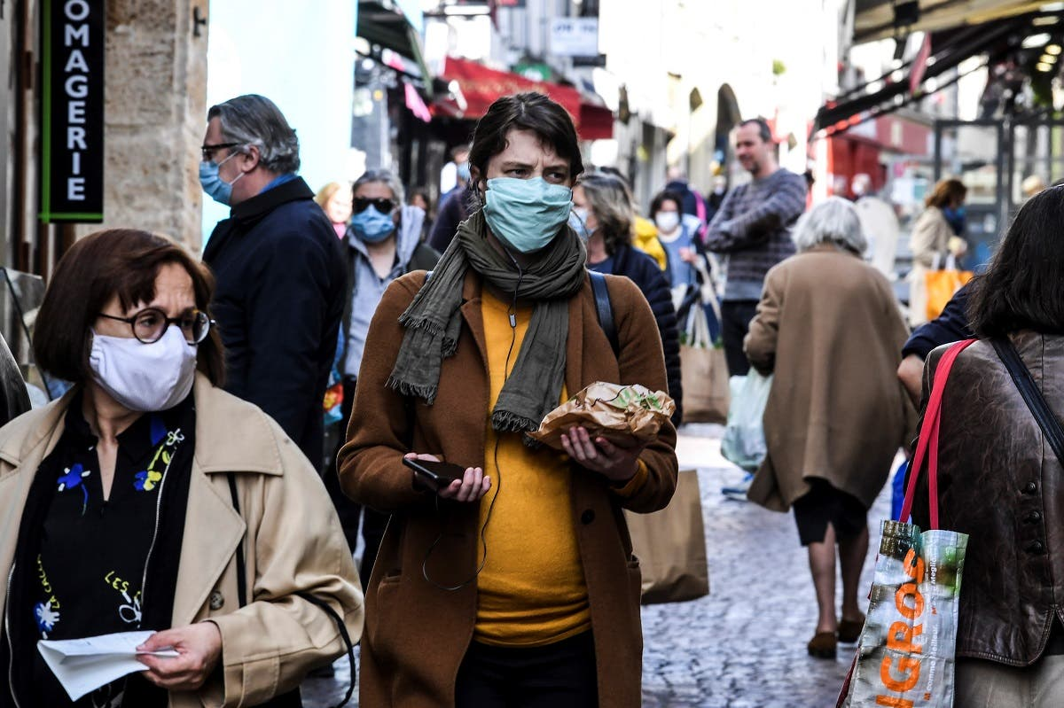 A woman wearing a protective facemask walks in the Mouffetard street as she does her grocery shopping during the food market, on May 2, 2020 in Paris. (AFP)