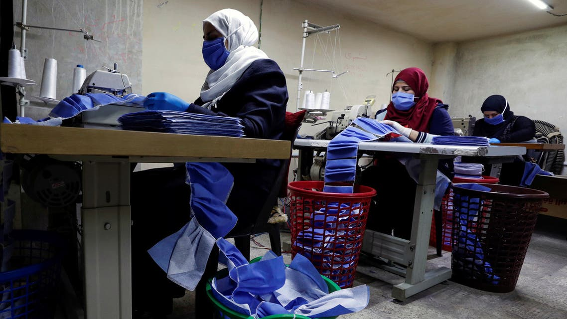 Workers make face masks in order to provide help to healthcare workers and hospitals to face the spread of coronavirus disease (COVID-19) at an atelier in Damascus, Syria April 16, 2020. Picture taken April 16, 2020. REUTERS/Omar Sanadiki