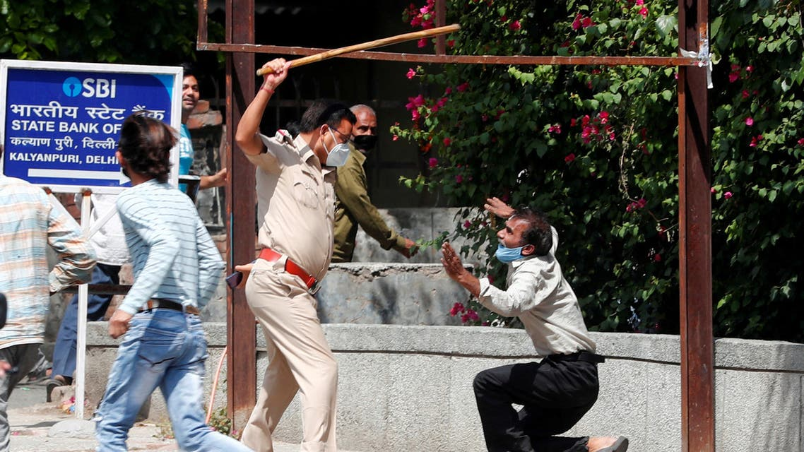 A police officer raises a baton at a man who, according to police, had broken the social distancing rule, outside a wine shop during an extended nationwide lockdown to slow the spread of the coronavirus disease (COVID-19), in New Delhi, India. (Reuters)