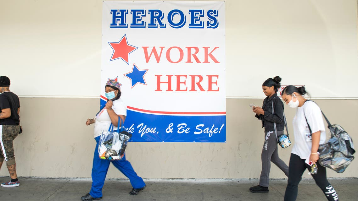 Employees walk by a sign Heroes Work Here outside of the Los Angeles USPS Plant on April 29, 2020, in Los Angeles, California.  (AFP)