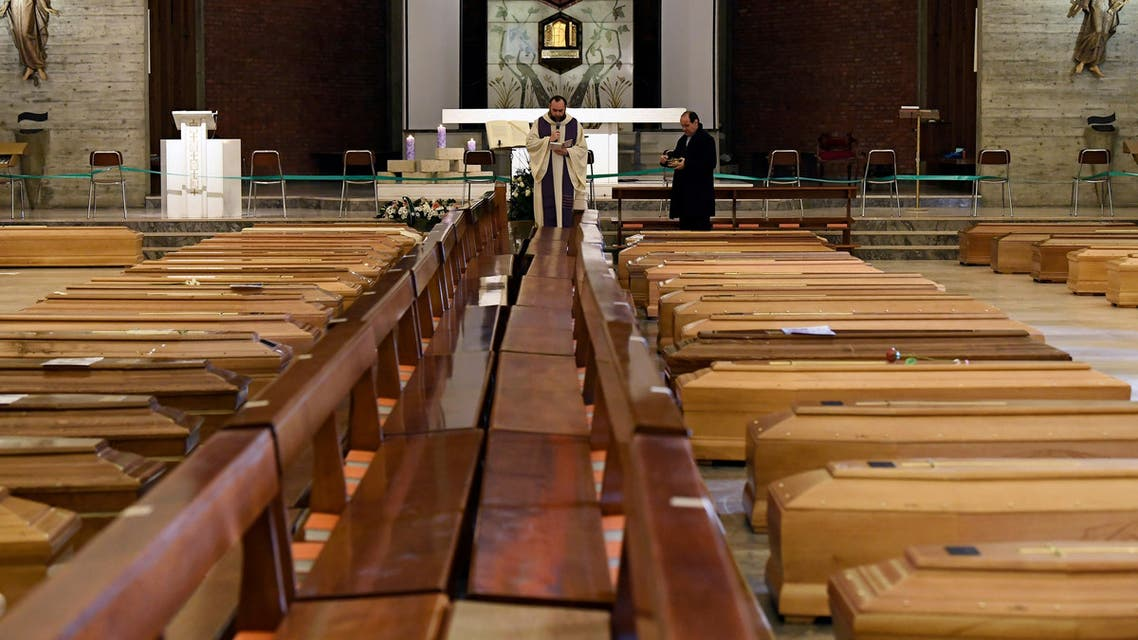 A local priest blesses coffins that have been piling up in a church due to a high number of deaths, before they are taken away by military trucks, as Italy struggles to contain the spread of coronavirus disease (COVID-19), in Seriate, Italy March 28, 2020. REUTERS/Flavio Lo Scalzo