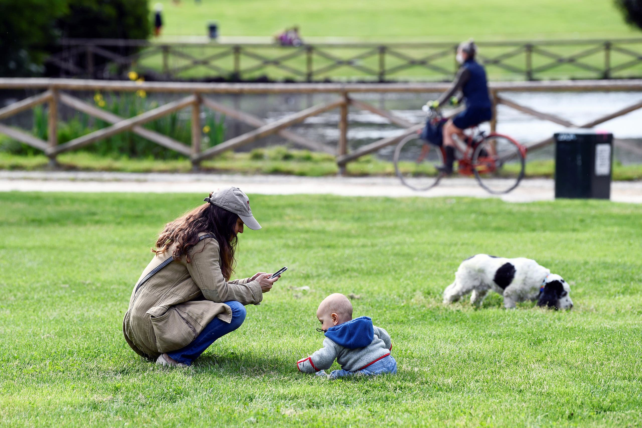 A woman uses her mobile phone at the Sempione park next to a baby, after parks reopen as Italy begins a staged end to a nationwide lockdown. (Reuters)