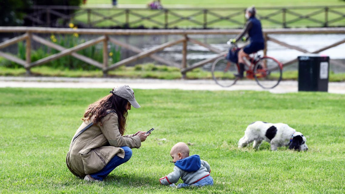 A woman uses her mobile phone at the Sempione park next to a baby, after parks reopen as Italy begins a staged end to a nationwide lockdown due to a spread of the coronavirus disease (COVID-19), in Milan, Italy, May 4, 2020. (Reuters)