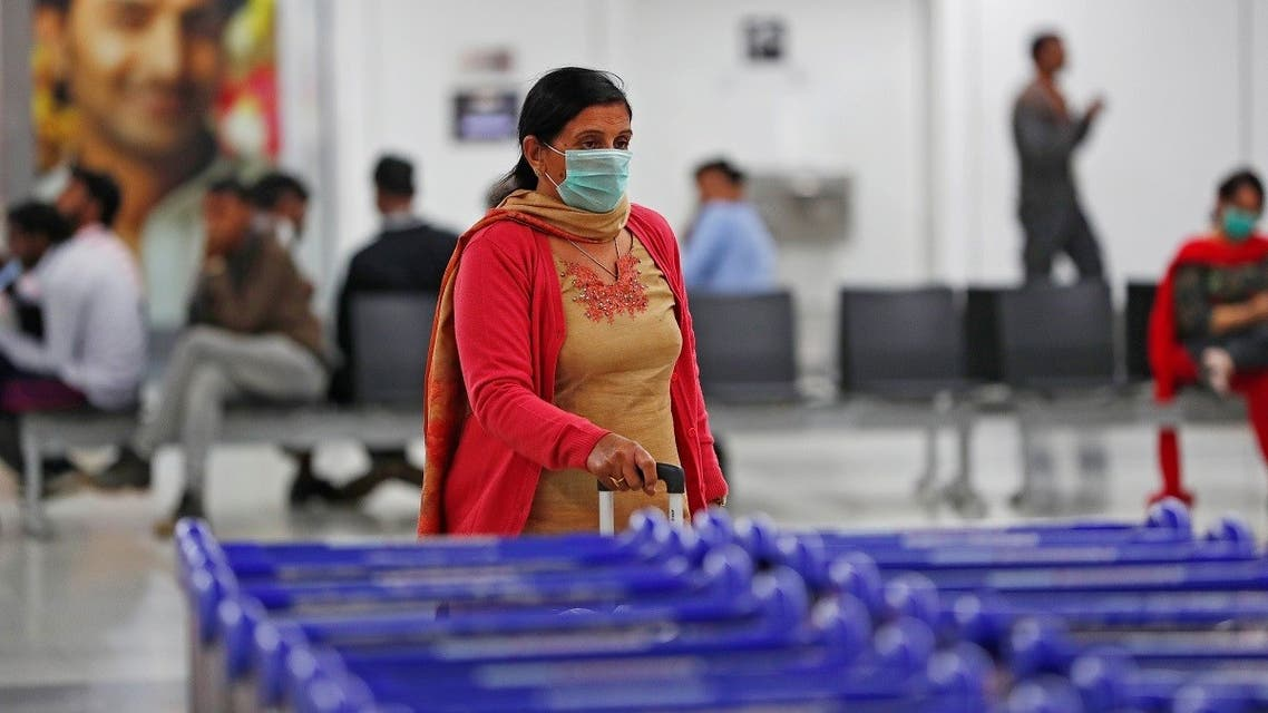 A passenger wearing a protective mask walks inside an airport terminal following an outbreak of the coronavirus disease (COVID-19), in New Delhi. (Reuters)