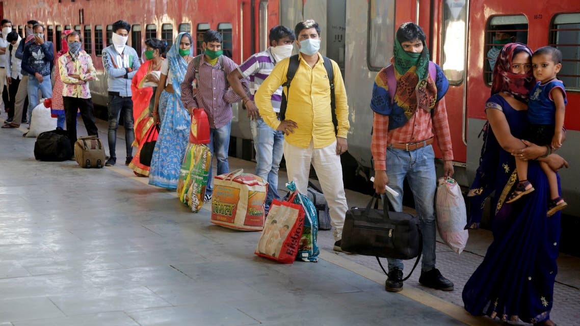Migrant workers wait to board a special train to return to Agra in Uttar Pradesh state, at a railway station in Ahmedabad, Gujarat, on May 2, 2020. (AP)