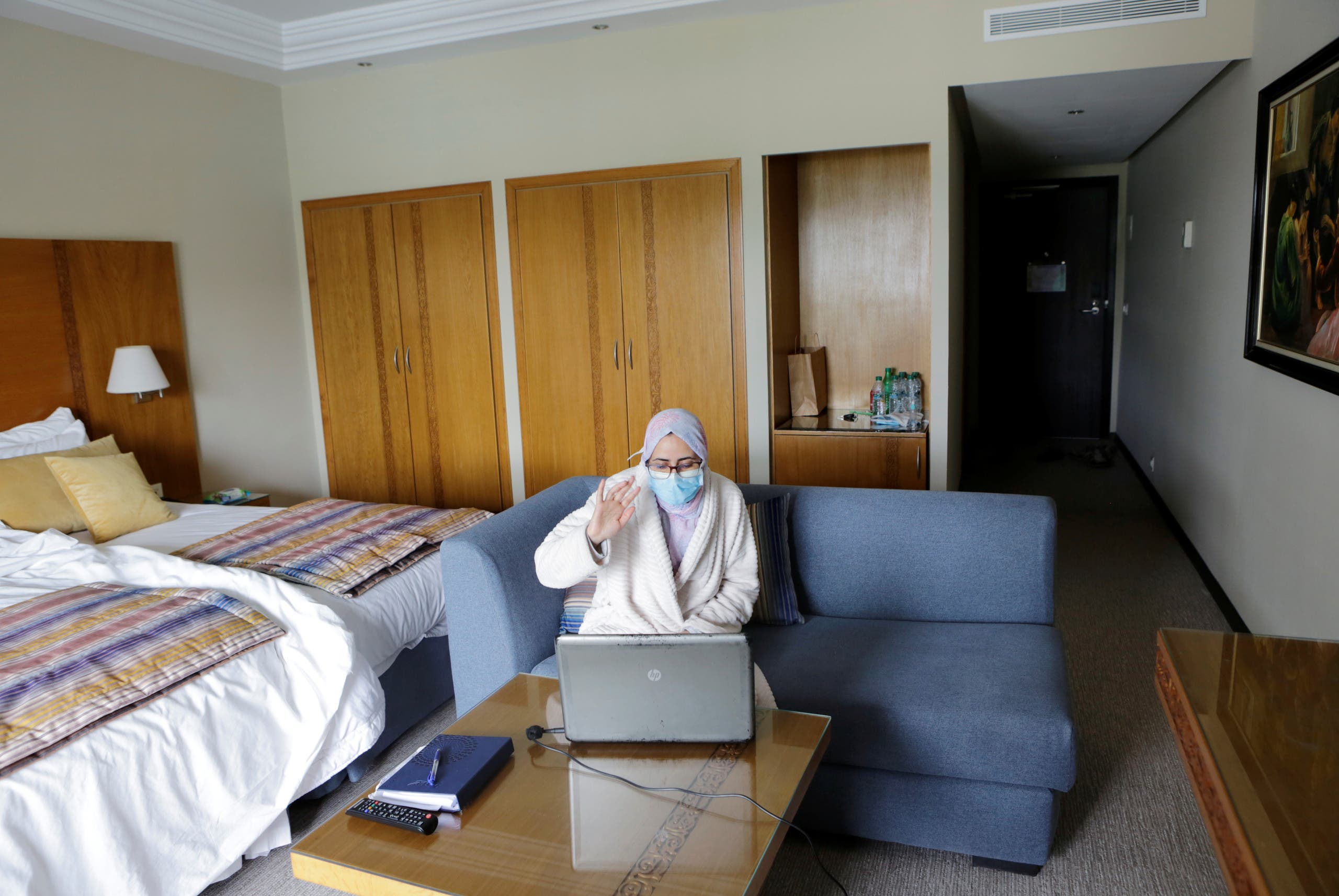 Nurse anesthetist Teimi Hakima uses a laptop to make a video call and speak with her family in her room at hotel Dawliz in Sale. (Reuters)