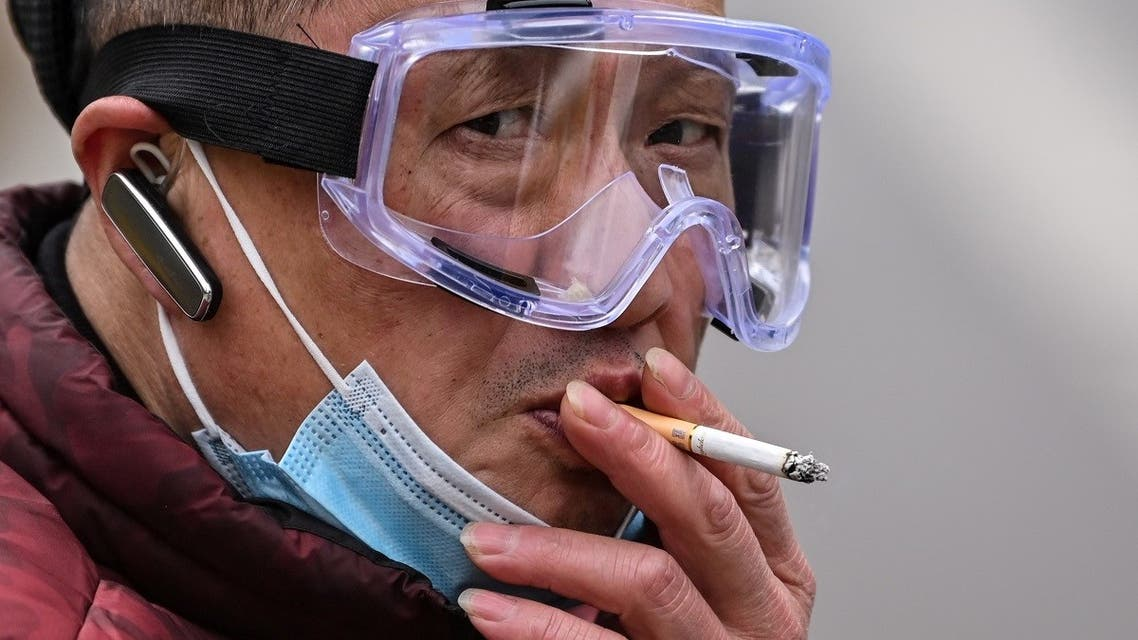 A man smokes a cigarette on his scooter in Wuhan, in China's central Hubei province on April 10, 2020. (AFP)