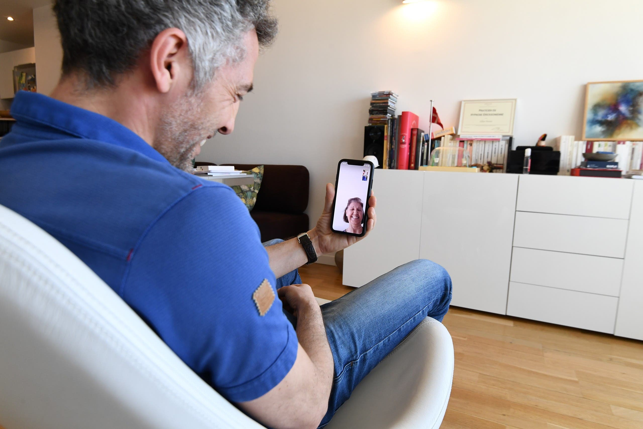 A man speaks with his mother via messaging app Whatsapp at an apartment in Paris on March 25, 2020. (AFP)