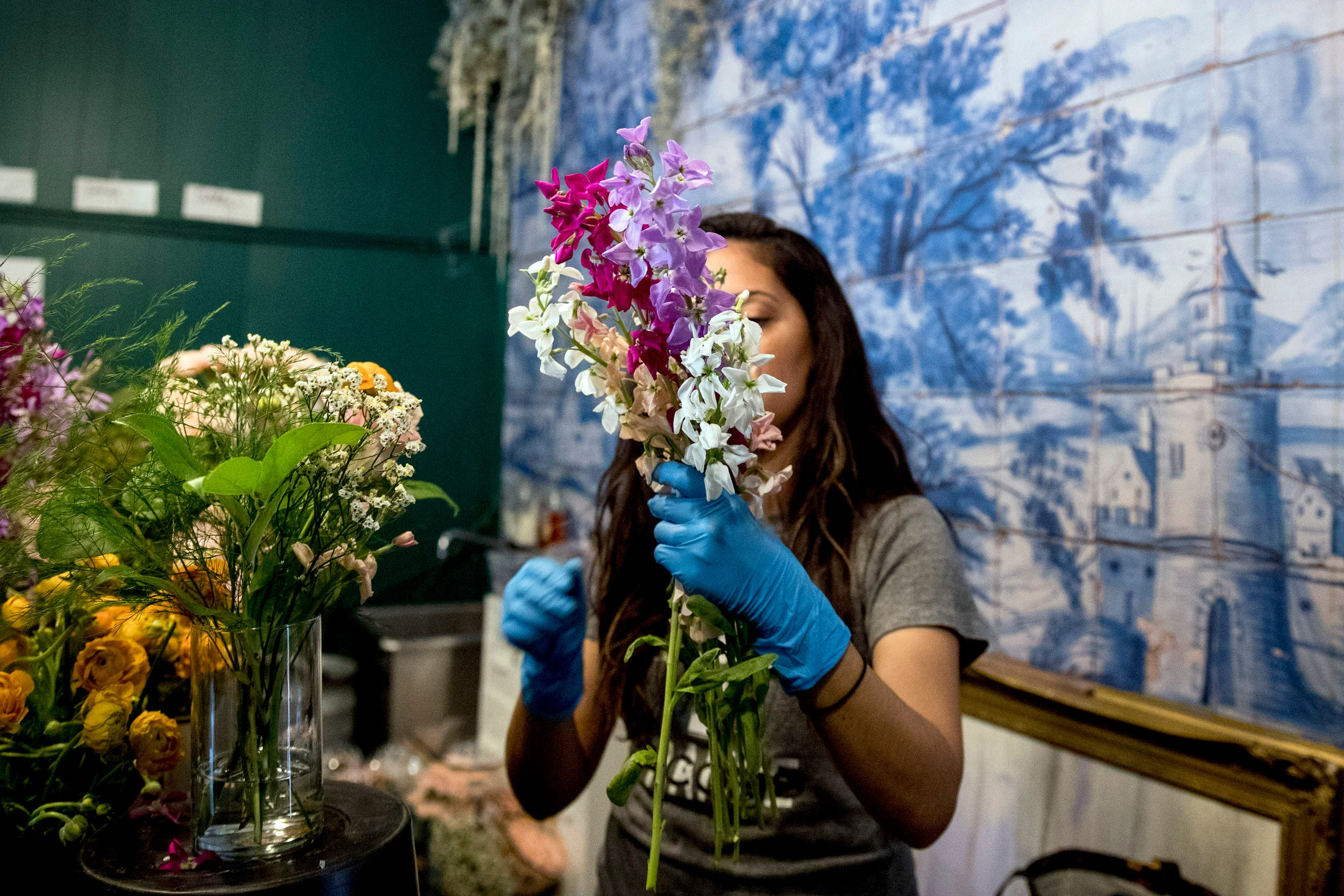 MJ Javan, prepares bouquets of flowers at the flower shop She Loves Me DC after they received an influx of orders during the coronavirus epidemic on March 20, 2020, in Washington. (AP)