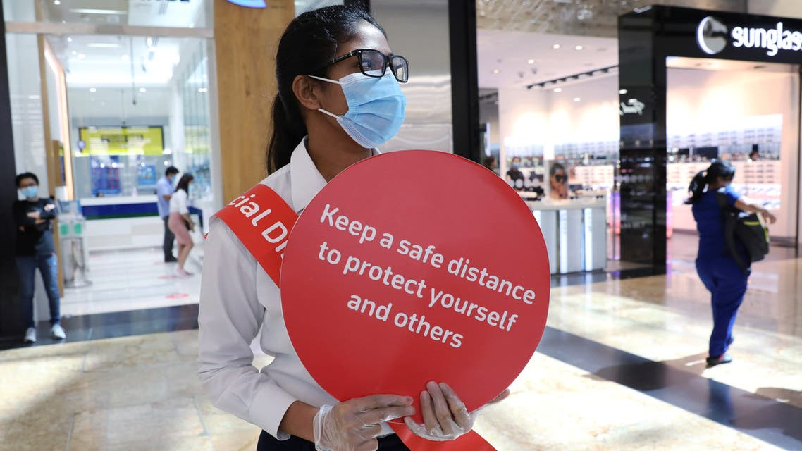 A woman wearing a protective face mask and gloves holds a sign at Mall of the Emirates after the UAE government eased a curfew and allowed stores to reopen, following the outbreak of the coronavirus in Dubai, United Arab Emirates, May 5, 2020. (Reuters)