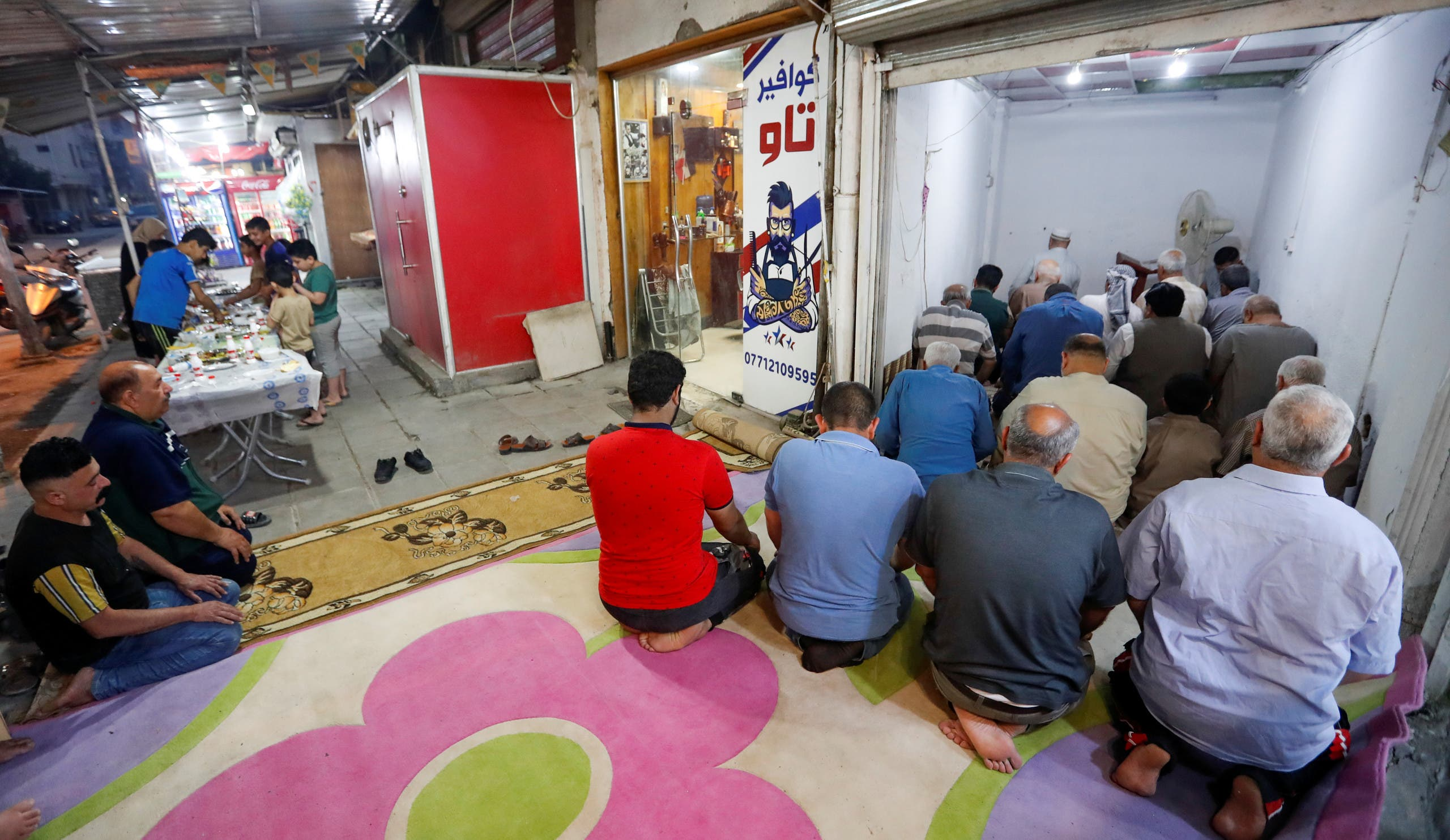 Iraqi muslims perform Ramadan prayers at a store, after the Iraqi government ordered all mosques to stay closed, during the holy fasting month of Ramadan, in Baghdad's Adhamiya district. (Reuters)