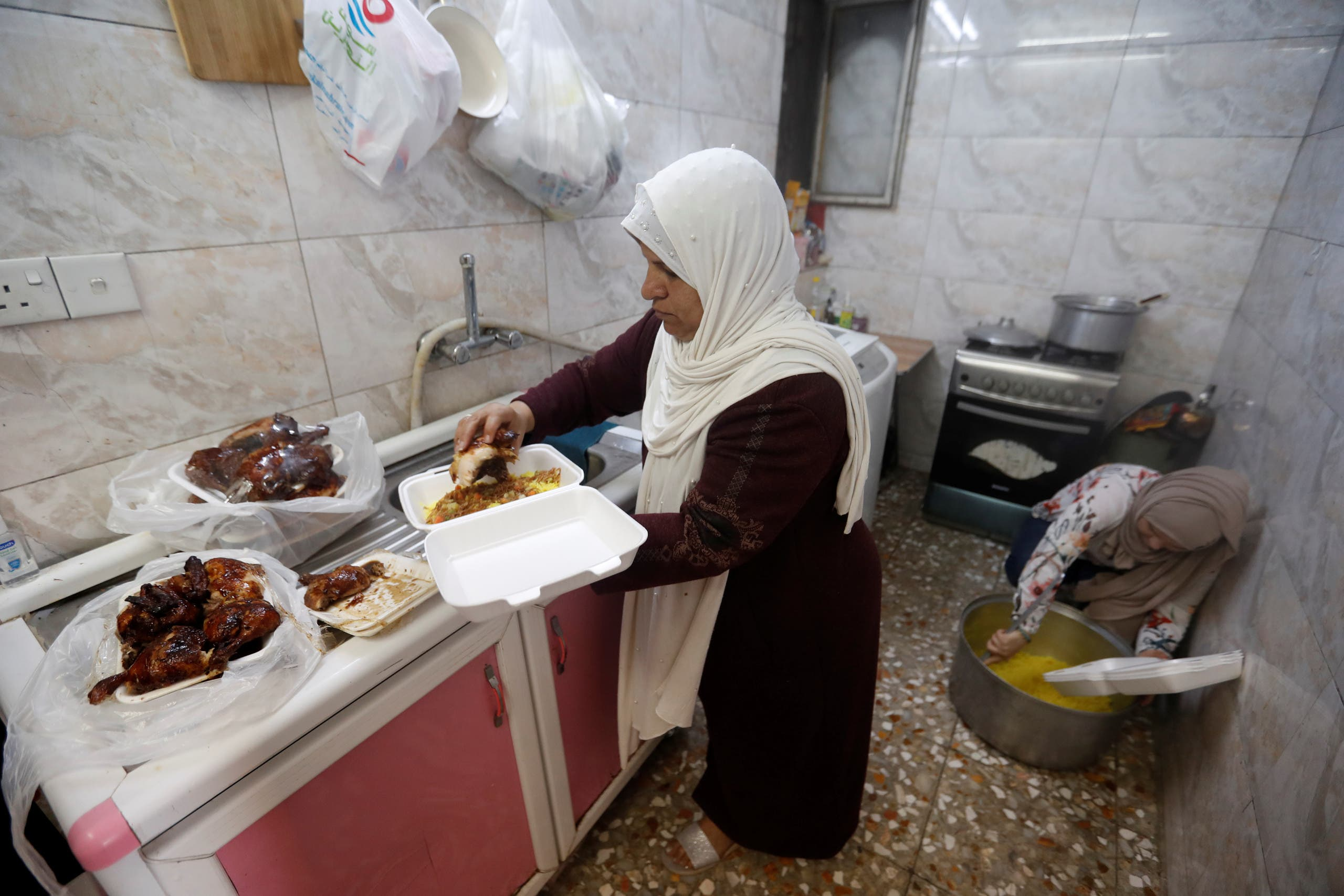 An Iraqi woman Ikhlas Majeed prepares Iftar meals for worshipers and poor families during the holy fasting month of Ramadan in Baghdad's Adhamiya district. (Reuters)