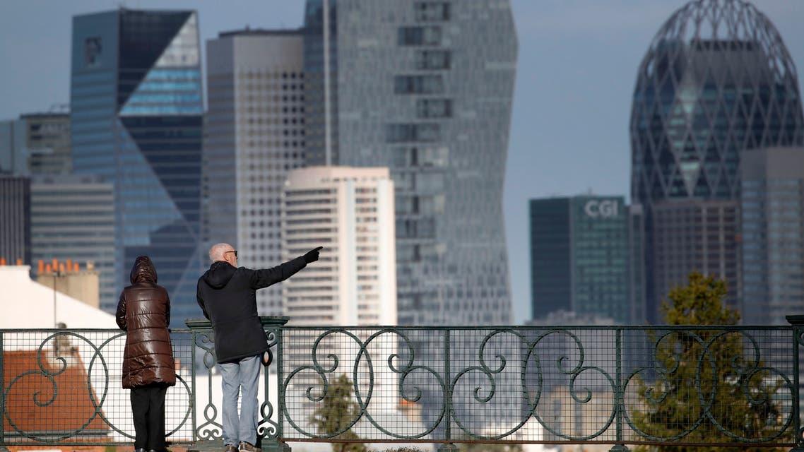A couple watch the business district of La Defense outside Paris, Thursday, March 12, 2020. (AP)