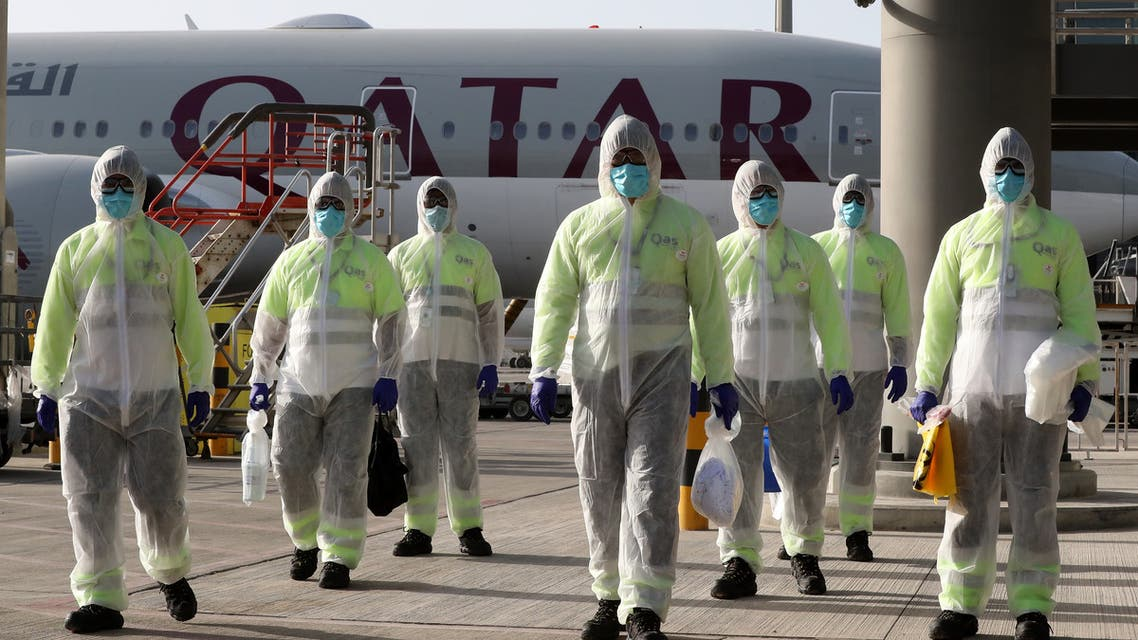 , wemployees of Qatar Aviation Services (QAS)earing protective gear as a safety measure during the COVID-19 coronavirus pandemic, walk along the tarmac after sanitising an aircraft at Hamad International Airport. (AFP)