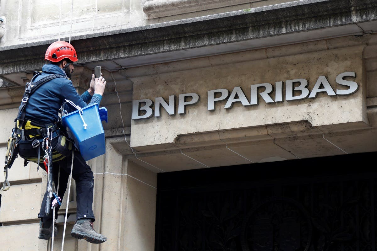 A worker cleans up the facade of a BNP Paribas bank office in Paris. (Reuters)