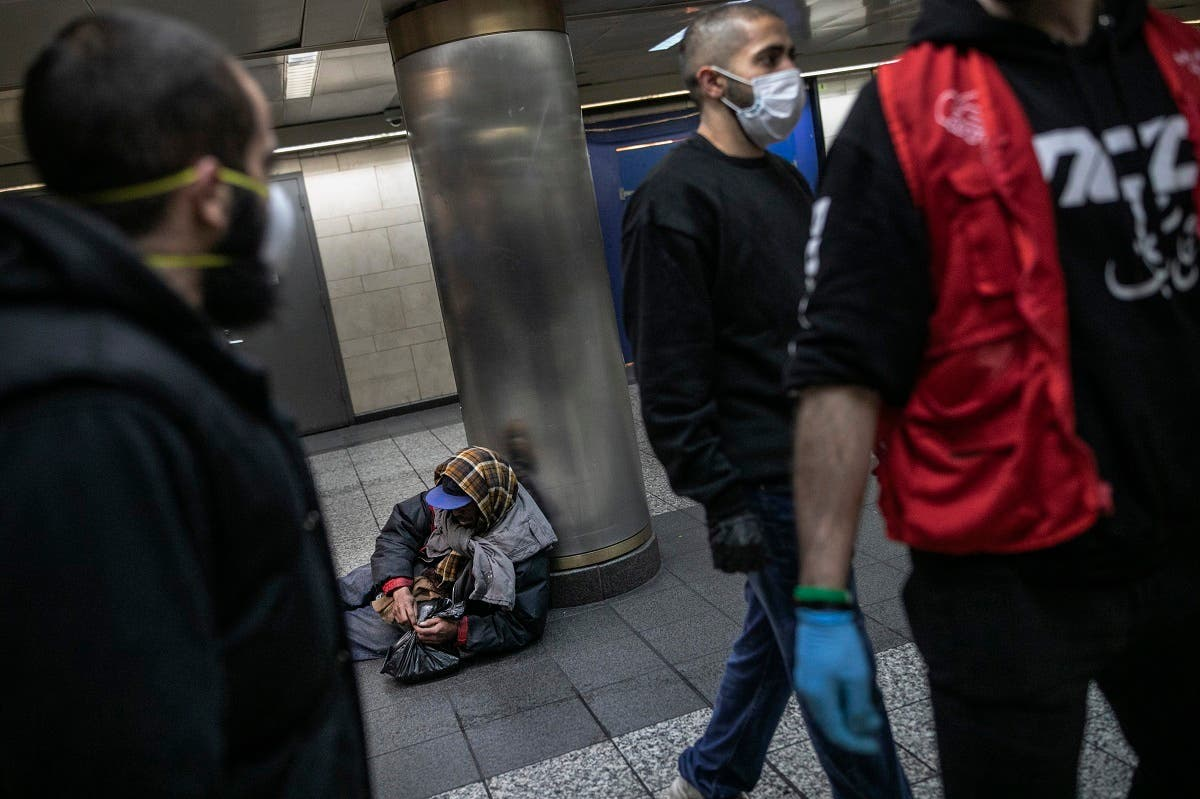 A homeless man in New York's Penn station opens a packet of food given to him by Hamza Deib, owner of Taheni Mediterranean Grill, center, and Mohammed Widdi, Coordinator at Muslims Giving Back, on Friday, May 1, 2020. (AP)