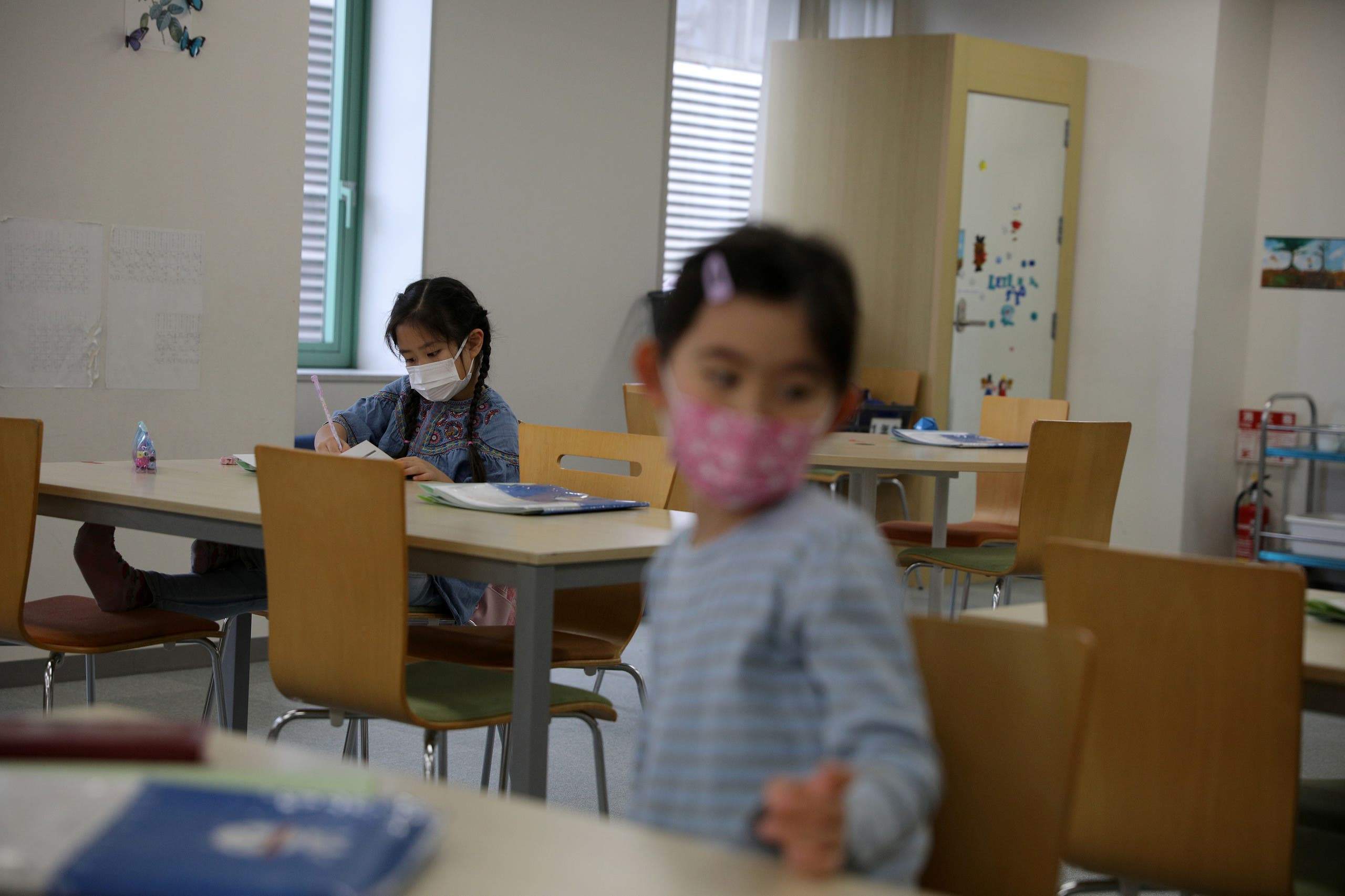 Children, wearing protective face masks, following an outbreak of coronavirus, are seen at a daycare center in Tokyo, Japan, March 5, 2020. (Reuters)
